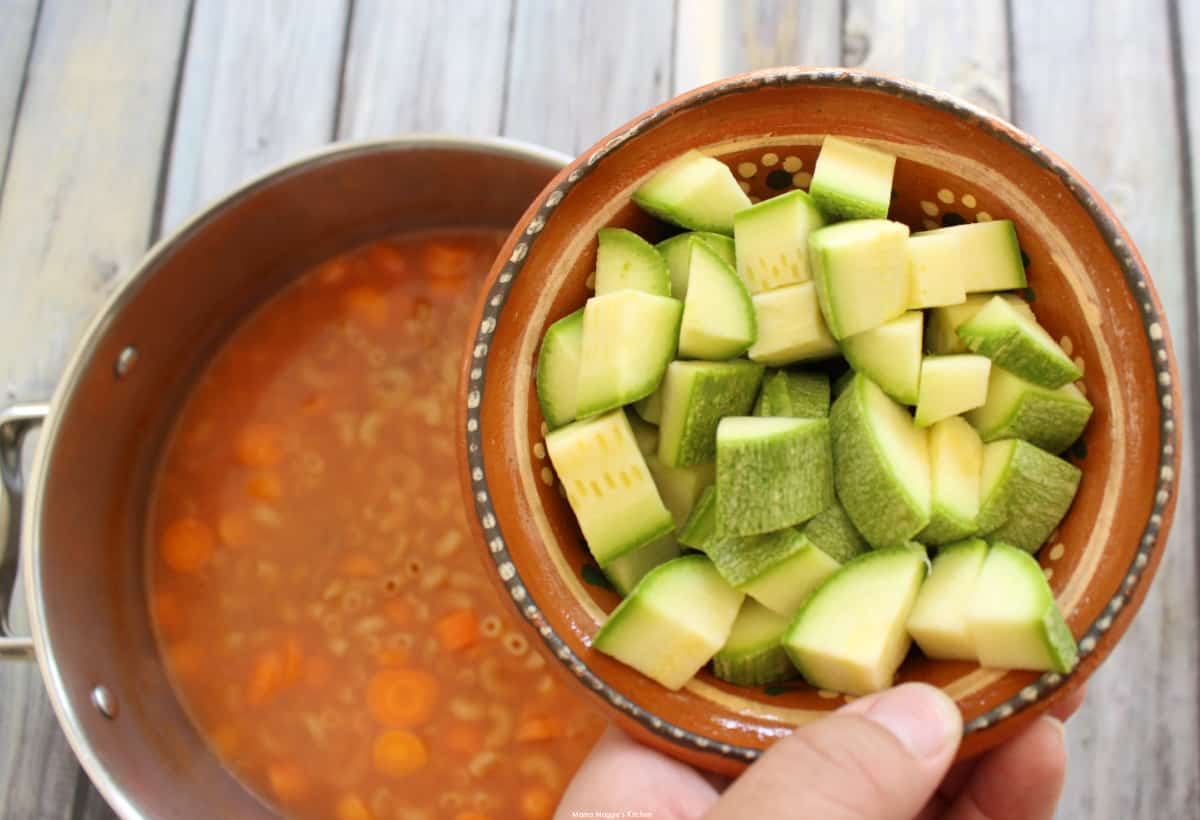 A hand holding a small bowl of diced calabacitas over a pot of soup.