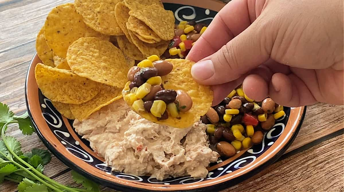A hand holding a chip with bean salad.
