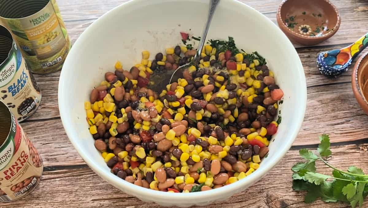 Bean salad in a large white bowl and a serving spoon.