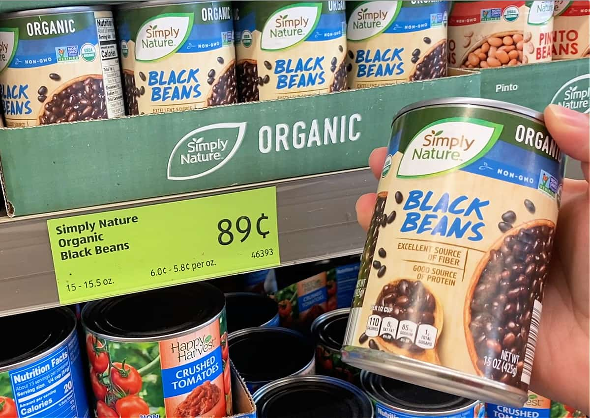 A hand holding a can of black beans at a grocery store.