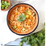 A bowl full of Sopa de Coditos next to sliced serranos and green cilantro.