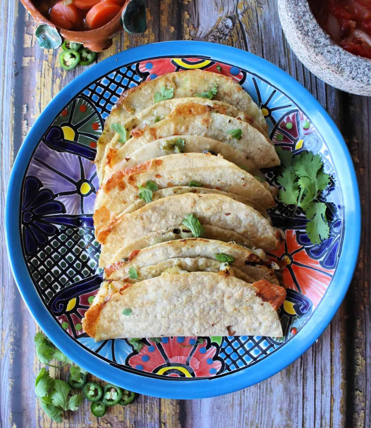 Tacos Gobernado stacked on a decorative blue talavera plate.