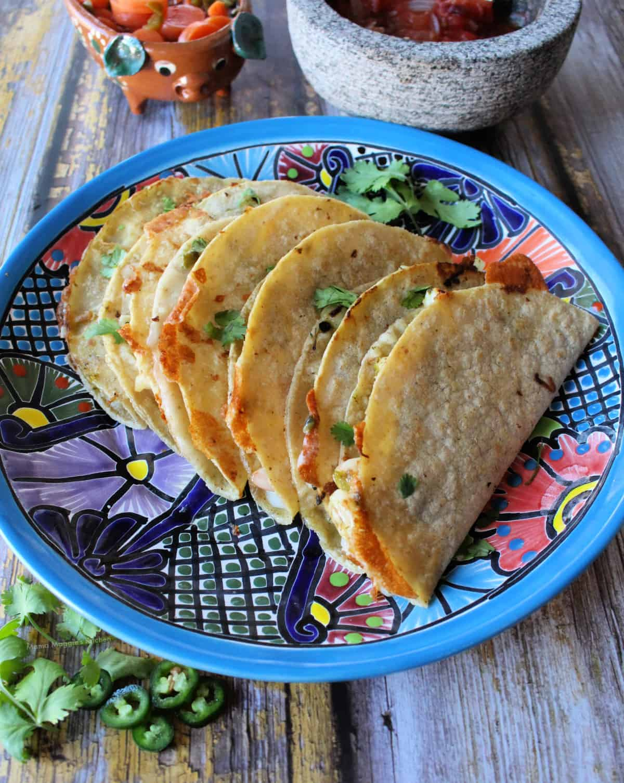 Tacos Gobernador stacked on a decorative blue talavera plate.