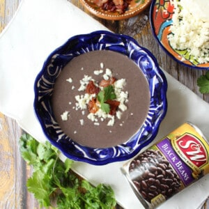Crema de Frjiol Negro served in a blue bowl and topped with queso fresco and bacon crumbles.