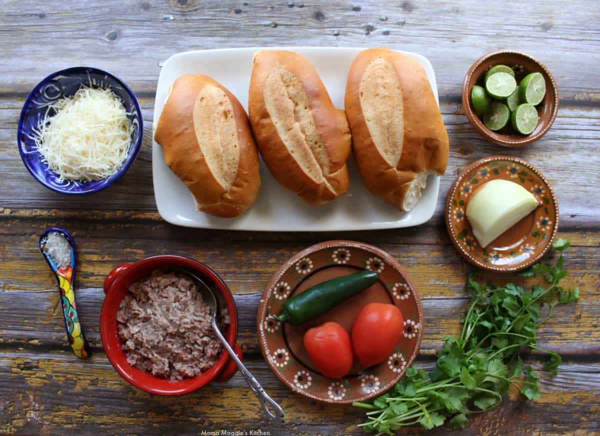 The ingredients to make molletes laid out on a wooden surface.