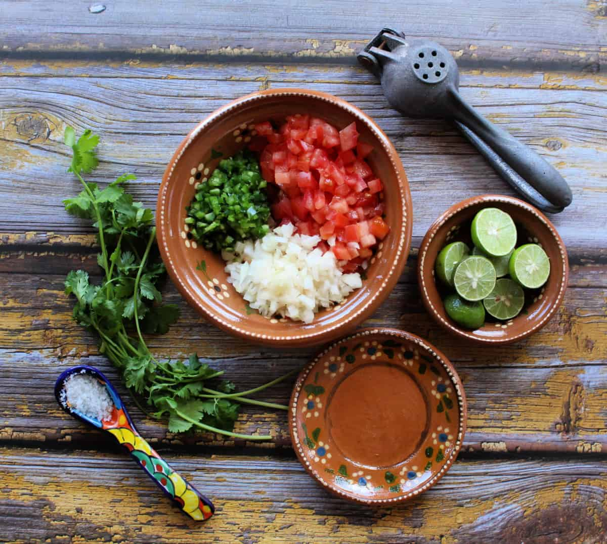 The ingredients to make pico de gallo in a Mexican clay bowl.