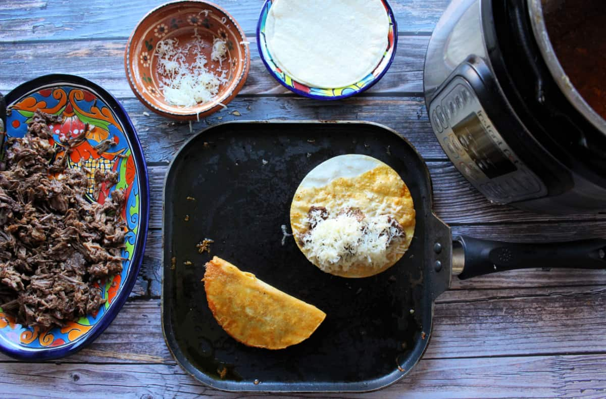 A skillet making the quesabirria tacos next to shredded beef and an instant pot.