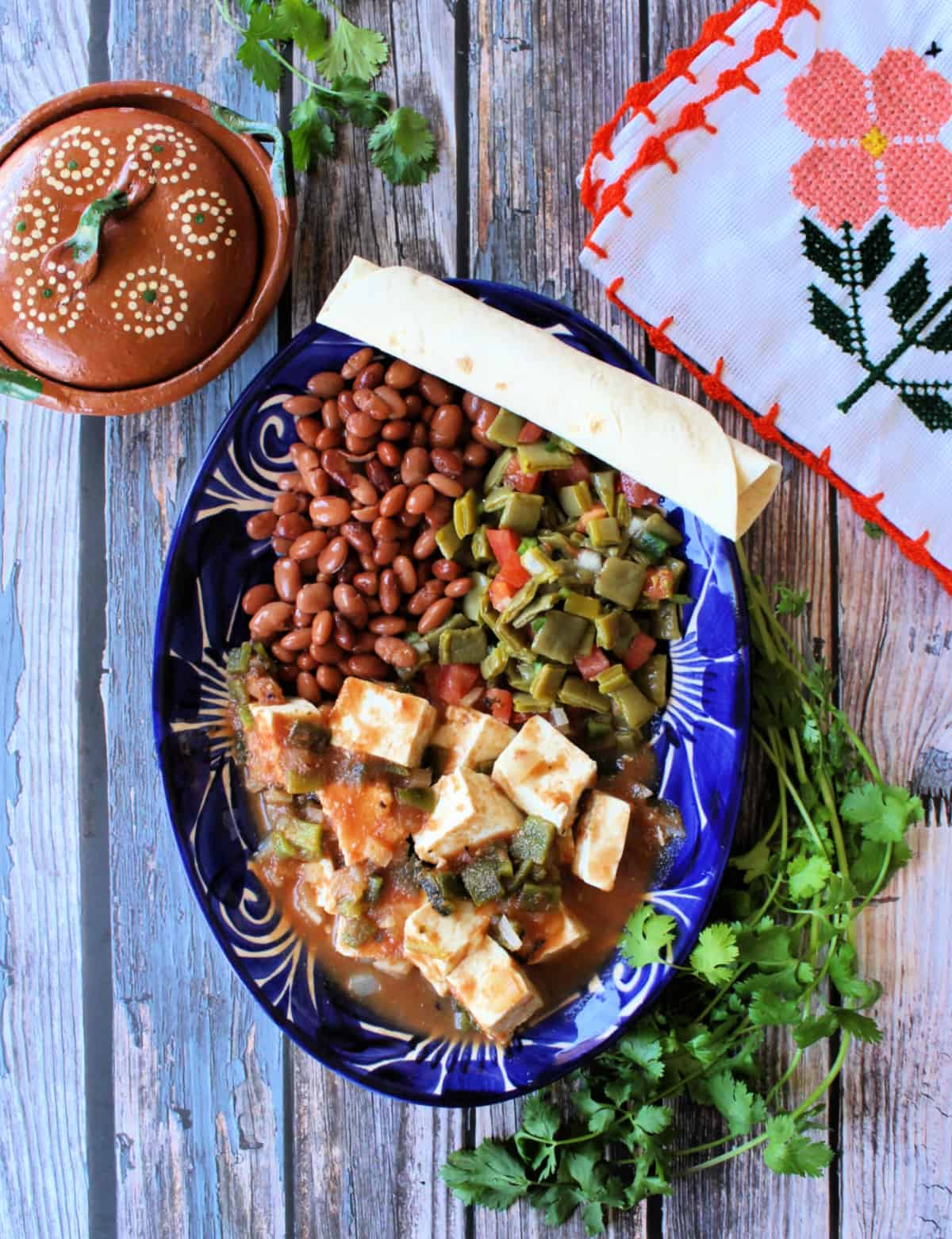 Queso con Chile served in a decorative blue plate next to pinto beans and a cactus salad.