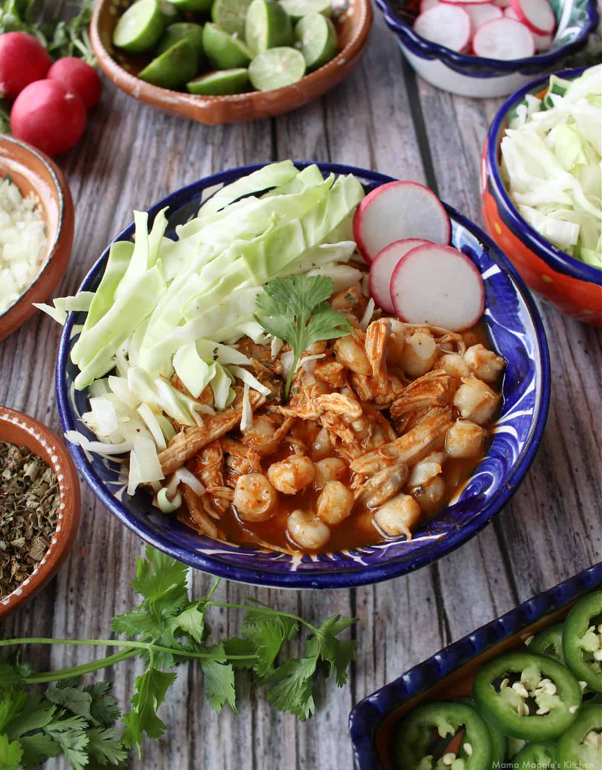 Red Chicken Pozole served in a decorative blue plate and surrounded by the toppings.