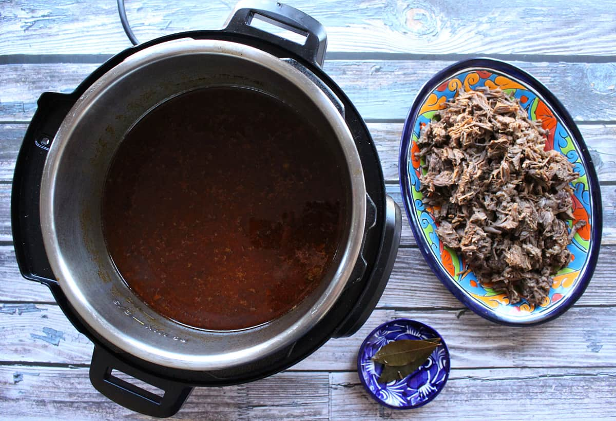 Shredded beef next to the beef broth still inside the instant pot.