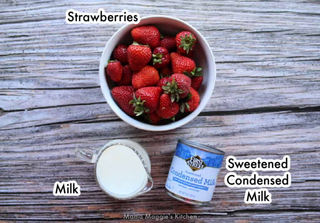 The ingredients needed to make the strawberry paletas labeled and spread out on a wooden surface.