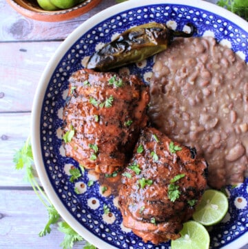 A blue plate with grilled chicken and refried beans.