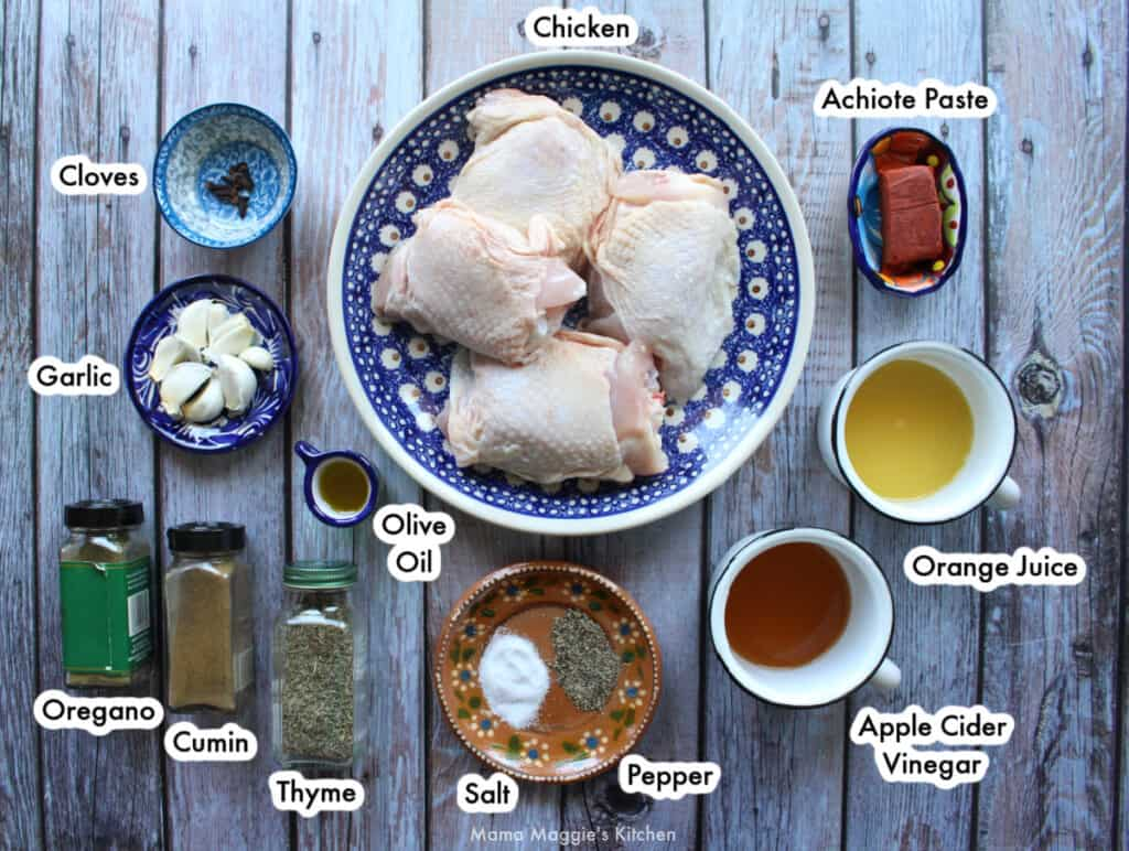 The ingredients needed to make Achiote Chicken labeled and spread out on a wooden table.