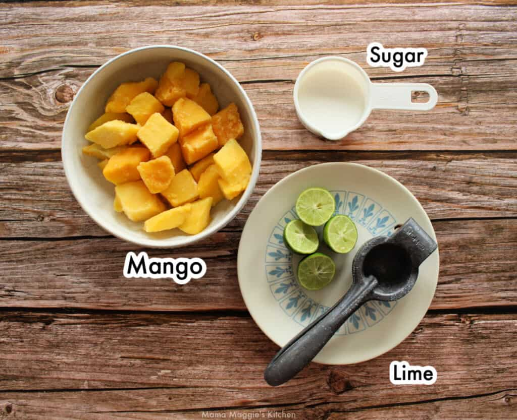 The ingredients to make Mango Paletas on a wooden table and labeled.