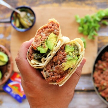 A hand holding two burritos, exposing the filling.