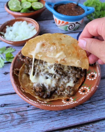 A hand pulling up the top tortilla showing the melted cheese inside mulitas.
