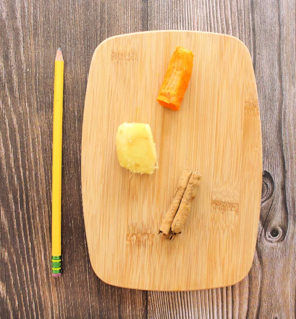 A cutting board with tumeric, ginger, and a cinnamon stick next to a pencil.