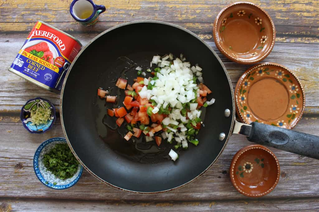 A skillet with onions, tomatoes, and jalapenos surrounded by decorative plates and other ingredients.