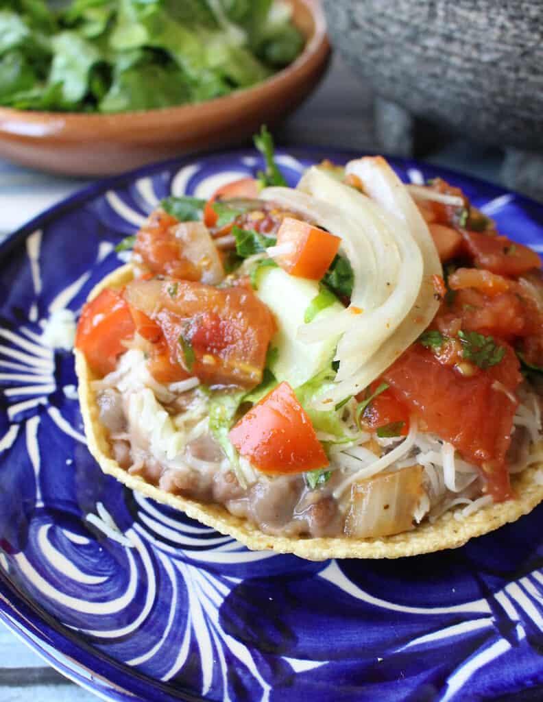 A bean tostada (tostadas de frijoles) served on a decorative blue plate.