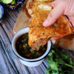 A hand holding a slice of birria pizza and dunking it into a cup with consomme.