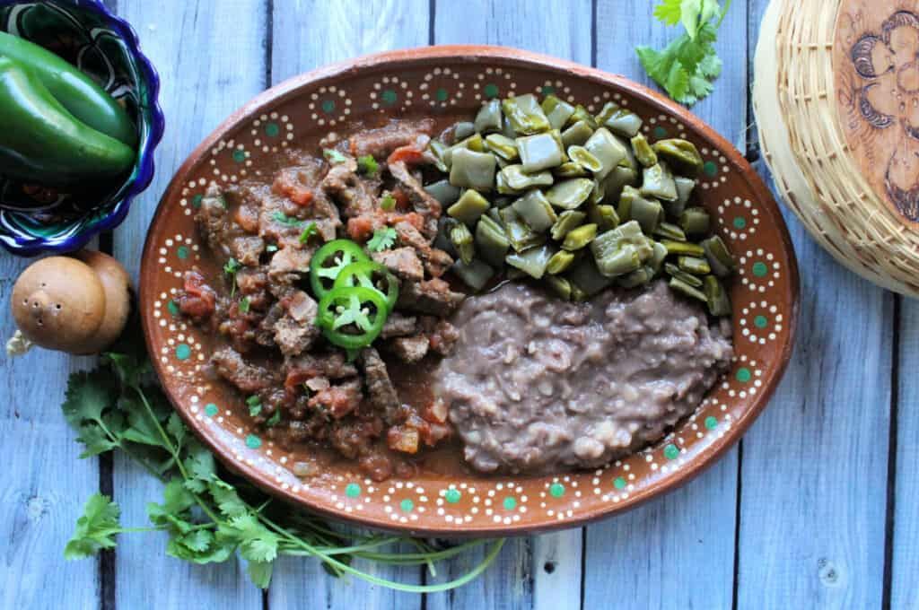 Bistec a la Mexicana served on a decorative clay plate next to beans and nopales.