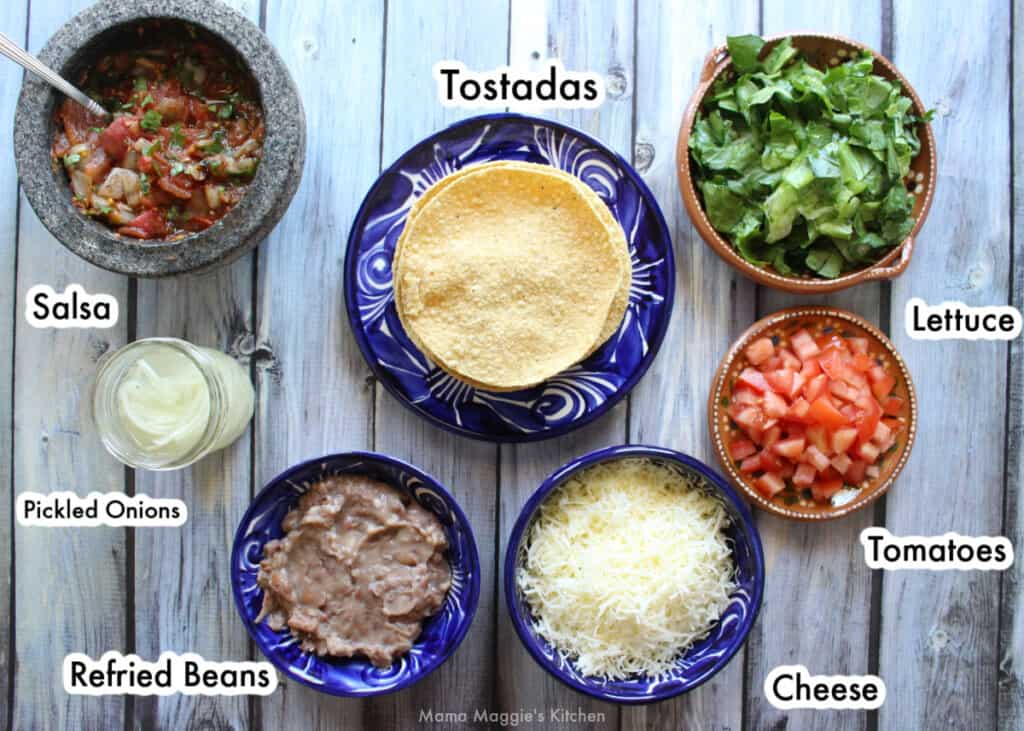 The ingredients needed to make bean tostadas on a wooden table and labeled.