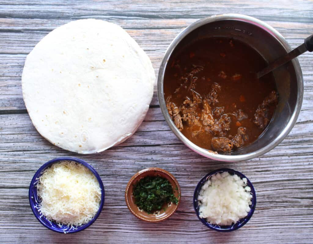 The ingredients needed to make birria pizza laid out on a wooden table.