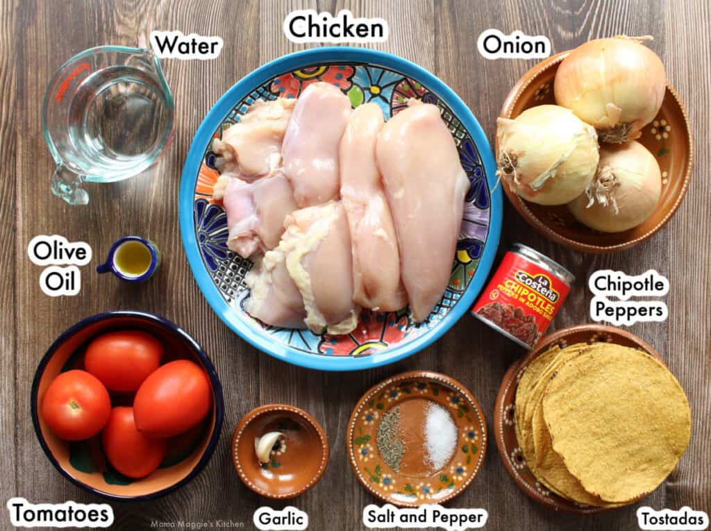 The ingredients necessary to make Chicken Tinga laid out and labeled on a wooden table.