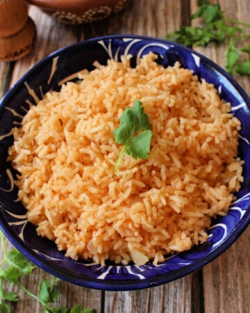 Arroz Mexicano (or Mexican Rice) served in a decorative blue plate and topped with a cilantro leaf.