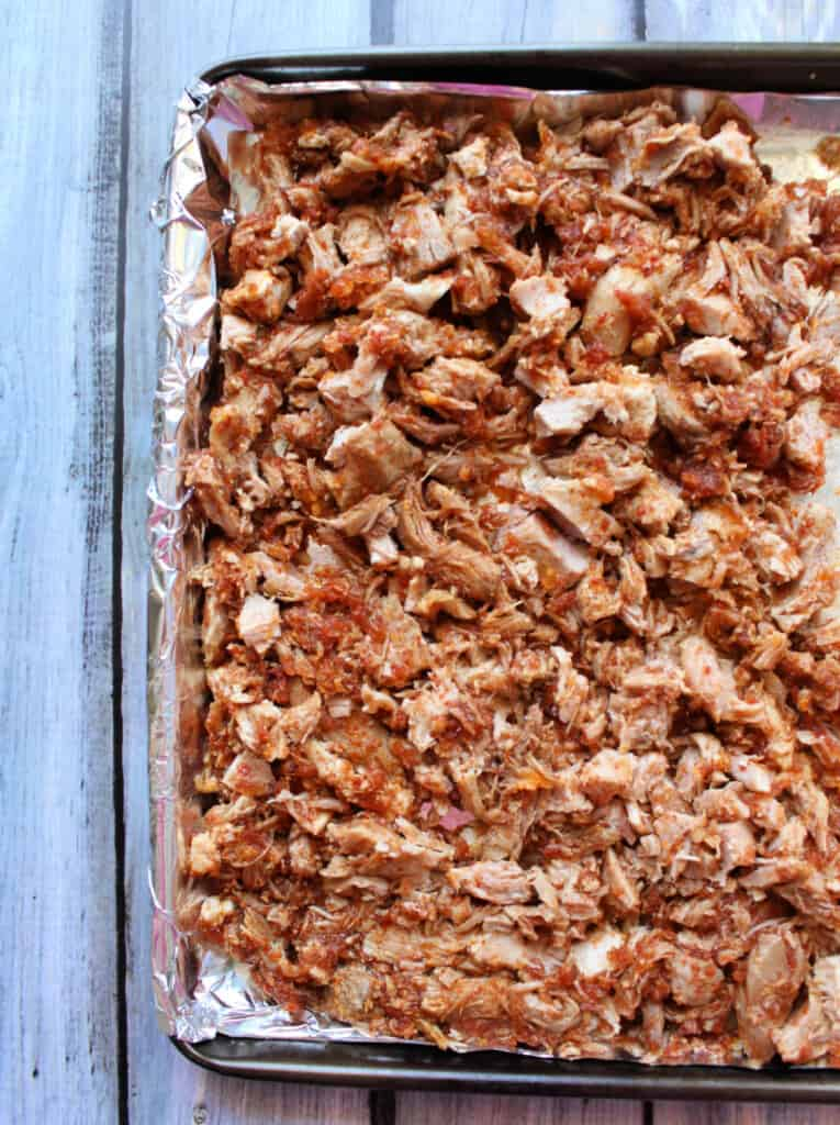 Cooked and shredded pork on a sheet pan lined with foil paper.