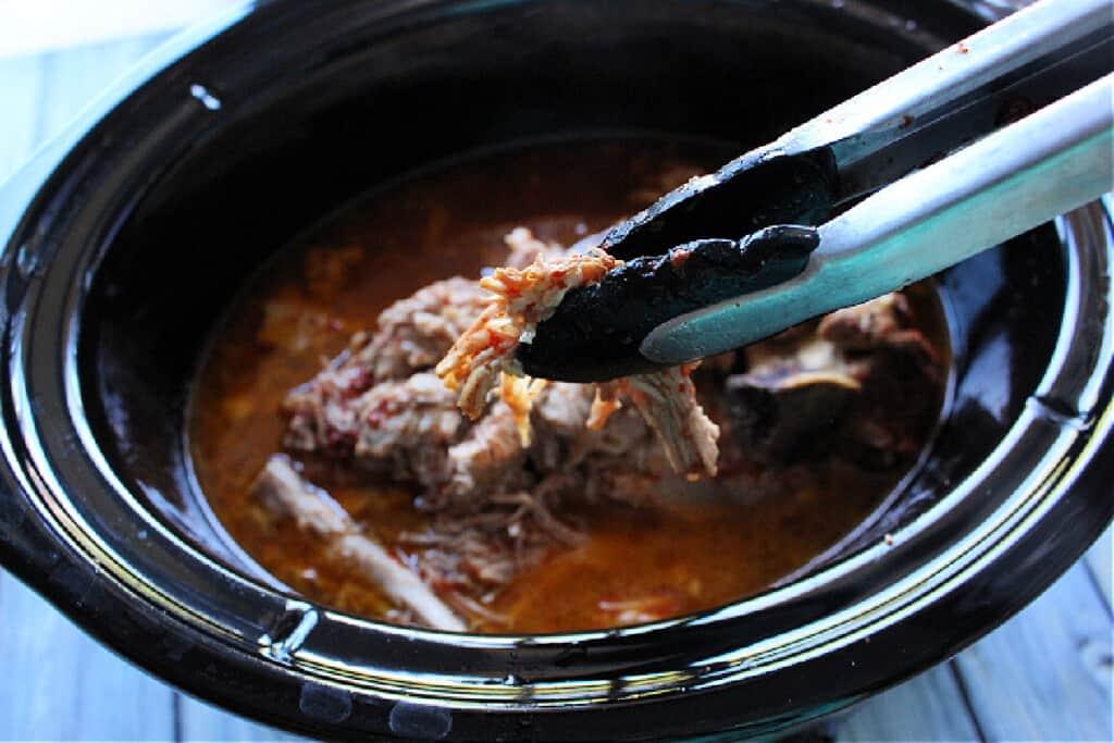 Tongs shredding pork inside a slow cooker.