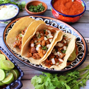 Slow cooker guajillo pork tacos served on a decorative plate next to the toppings.