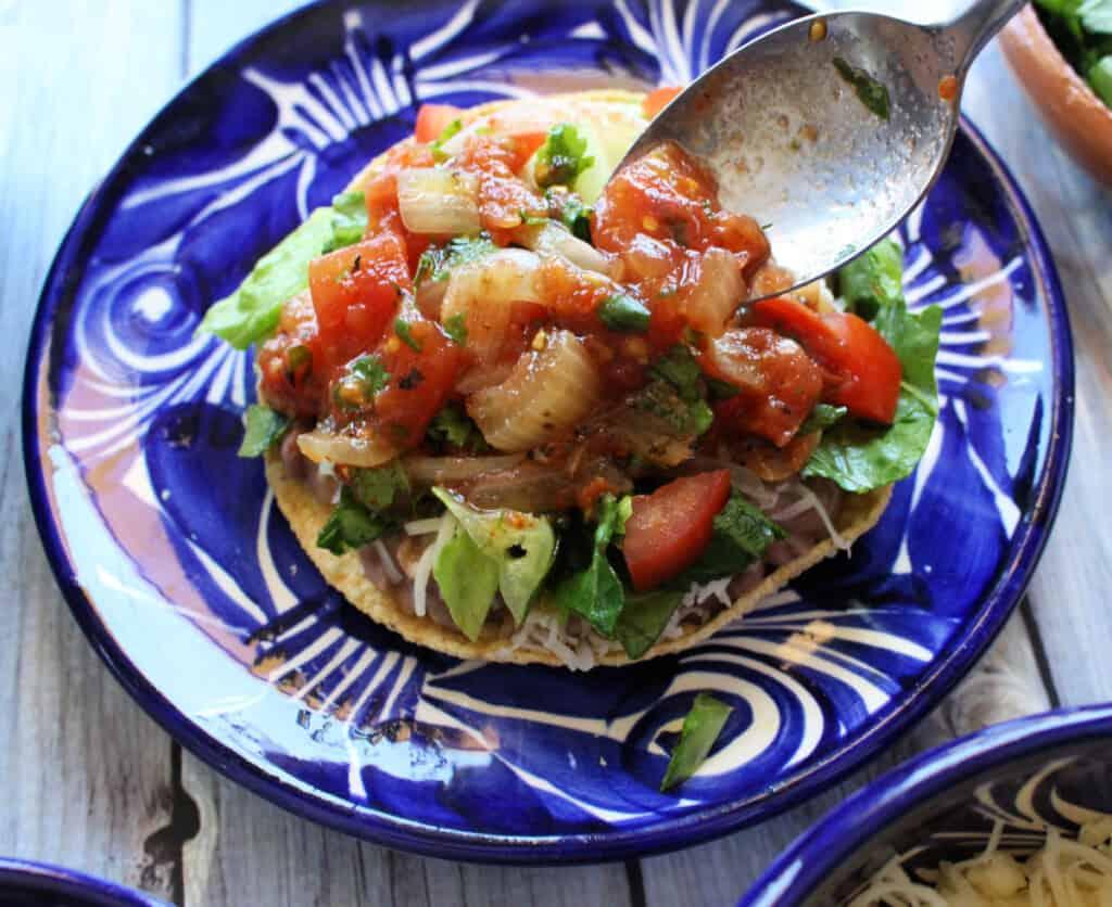 A spoon adding salsa to a bean tostada.