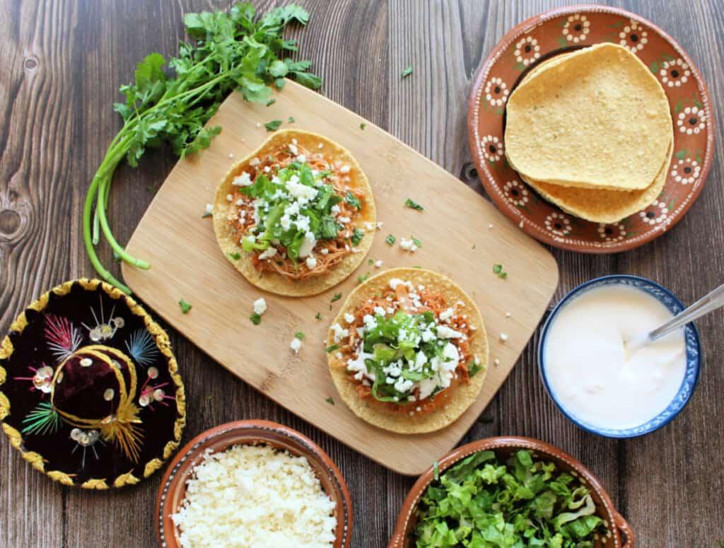 Two tostadas of Tinga de Pollo (Chicken Tinga) on a wooden board next to the toppings.