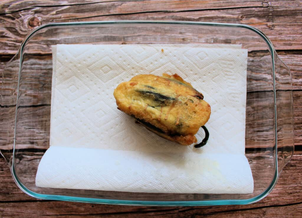 A chile relleno sitting on a white paper towel, draining any excess oil.