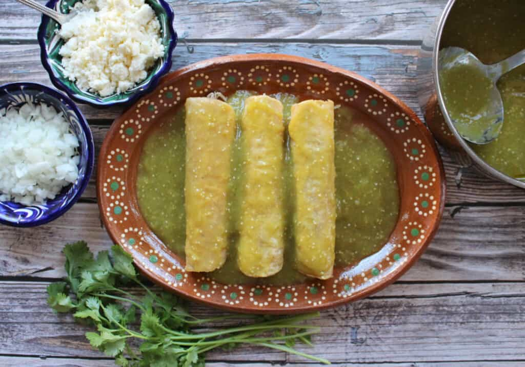 Chicken Enchiladas Salsa Verde served on a clay plate and surrounded by toppings.