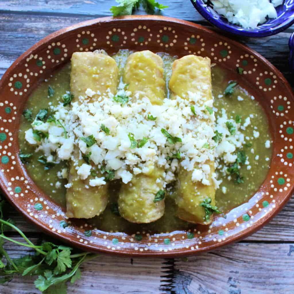 Enchiladas Verdes served on a decorative clay plate and topped with cheese and cilantro.