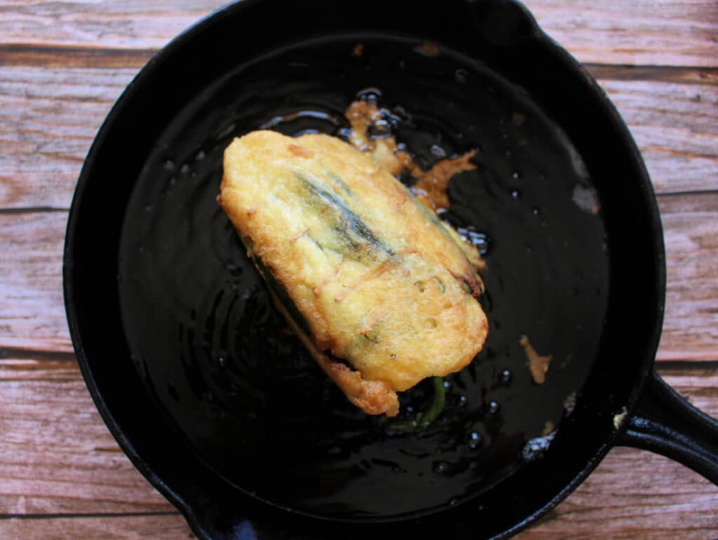 A chile relleno frying in a black iron skillet.