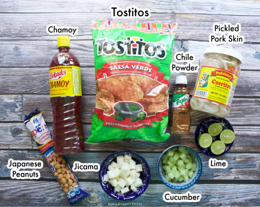 The ingredients needed to make Tostilocos labeled and sitting on a wooden table.