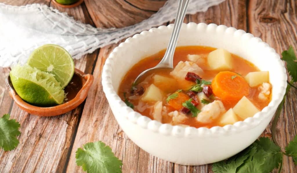 Caldo de Pescado served in a white bowl next to lime and cilantro leaves.