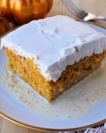 A slice of Pumpkin Pastel de Tres Leches served on a plate and topped with whipped cream.