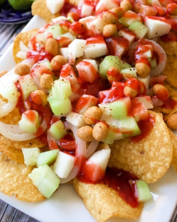 A plate of Tostilocos next to bowls with the ingredients needed to make the recipe.